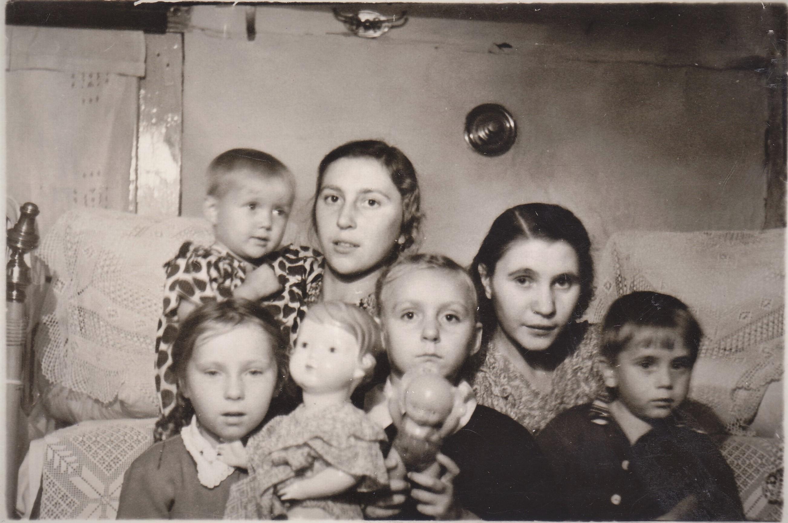На фото: слева с большой куклой сестра Оля, справа - я, за моей спиной крёстная, тётя Римма.