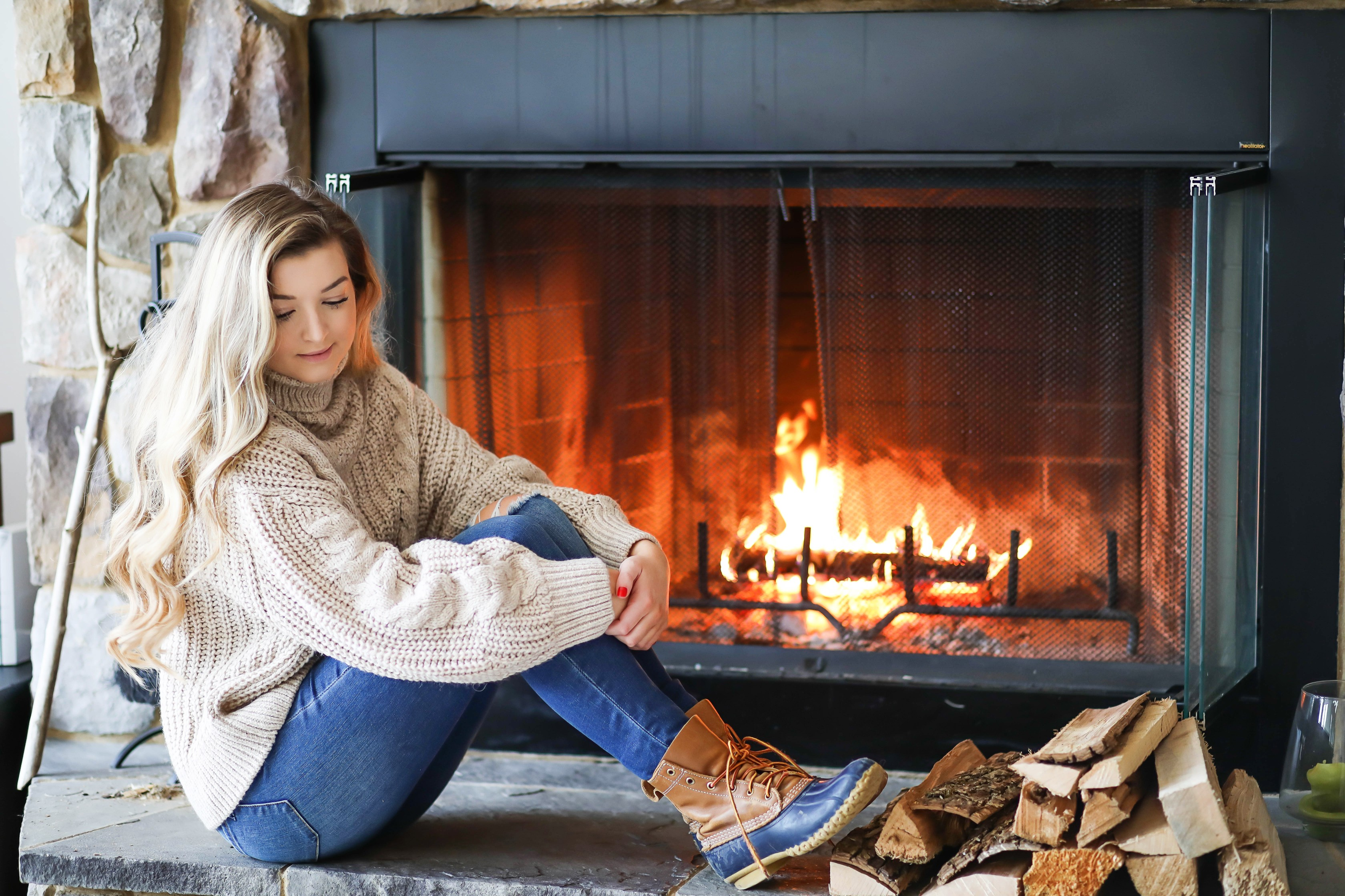 Cozy cableknit sweater infront of fireplace winter cable knit sweater fashion blog daily dose of cha